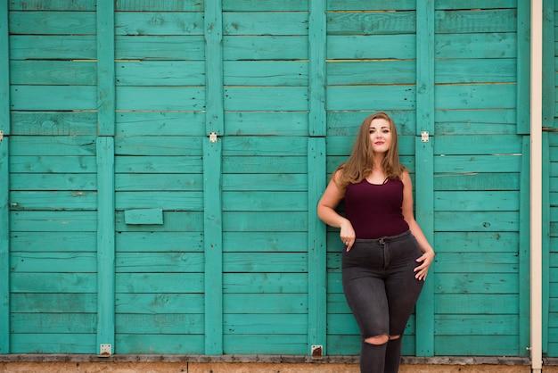 Blond meisjesmodel plus grootte op groene muur