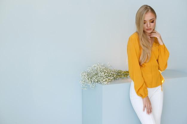 Blond met lang haar op een modieuze monochromatische achtergrond