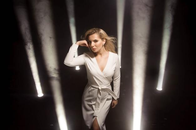 Blond mode meisje met lang en glanzend krullend haar. mooi model in witte jurk op het podium met verlichting.