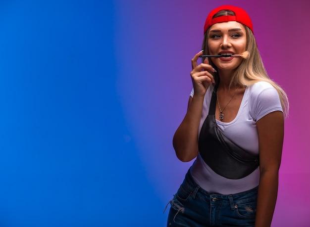 Blond model dat sportoutfits draagt en make-up toepast.