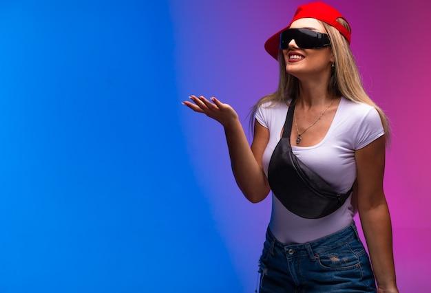 Blond model dat sportoutfits en zonnebril draagt die iets vraagt.