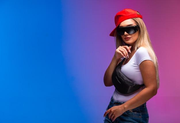 Blond model dat sportuitrustingen en zonnebril draagt.