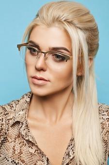 Blond model met blauwe ogen en perfecte huid in glazen op blauwe muur