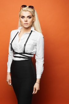 Blond model met perfecte body in zwarte strakke rok en in witte blouse poseren op oranje muur