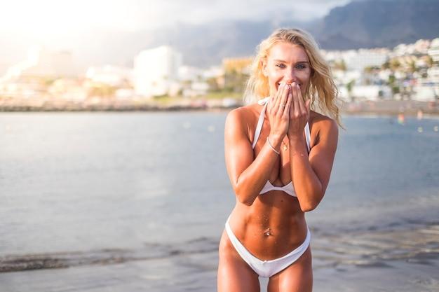 Blond mooi lang haar en mooie buikspieren vrouw en stuur een kus. zomervakantie op het strand met zon. reizen en genieten van lifestyle concept