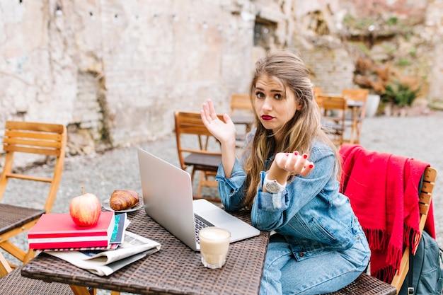 Blond mooi meisje, bezorgd en verrast, kan geen verbinding maken met openbare wifi op het terras.