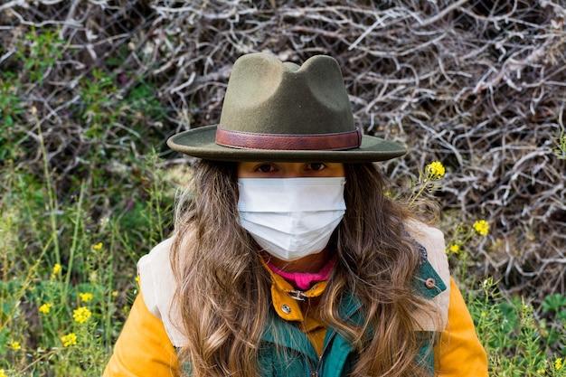 Blond ontdekkingsreizigermeisje met masker, groen vest en groene hoed. voorbereid om het coronavirus het hoofd te bieden.