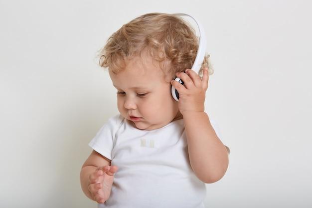 Blond peuter dragen witte t-shirt spelen met koptelefoon