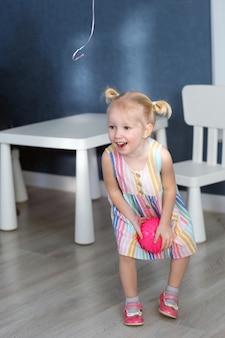 Blond peuter meisje in jurk spelen met bal binnenshuis kind plezier op verjaardagsfeestje. verticaal