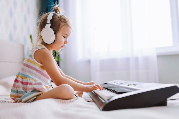 Blond peutermeisje met grote oortelefoons speelt klassieke digitale piano thuis zittend op bed. online onderwijsconcept, quarantaine.
