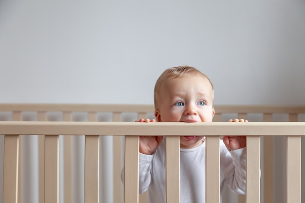 Blond schattig blauwogige kleine baby in witte romper bijten houten bed hoofdeinde op wit interieur