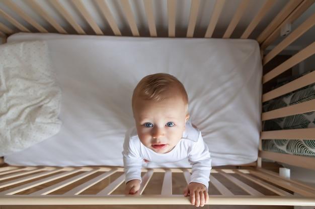 Blond schattig llittle kind in witte romper staat in houten bed