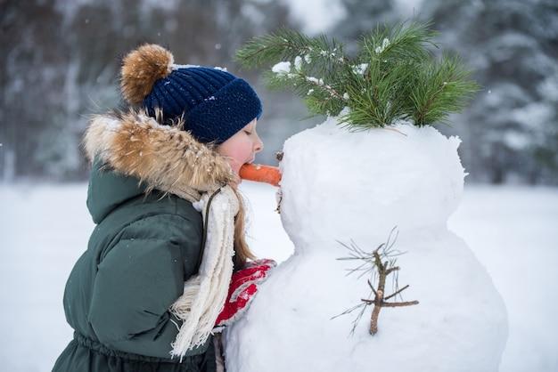 Blond schattig meisje gelukkig kind sneeuwpop wortel neus eten