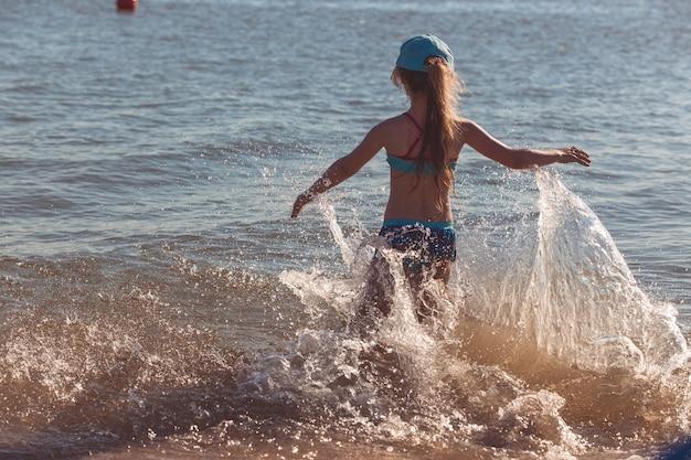 Blond schattig zevenjarig meisje dat plezier heeft en plezier heeft aan zee tijdens de vakantie.