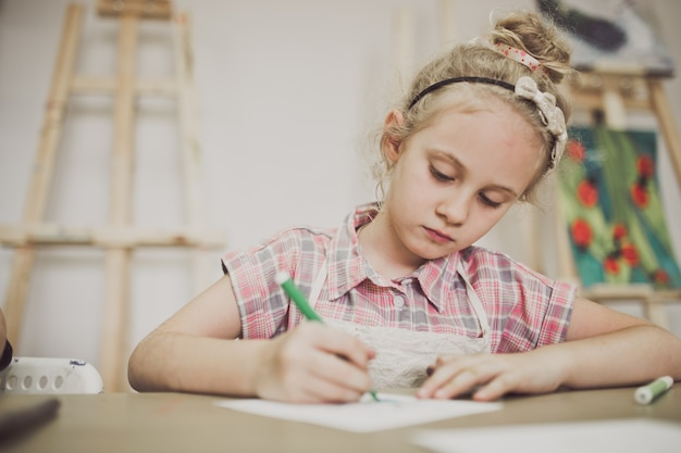 Blond schattig zevenjarig meisje, tekent aan de tafel in de creatieve studio.