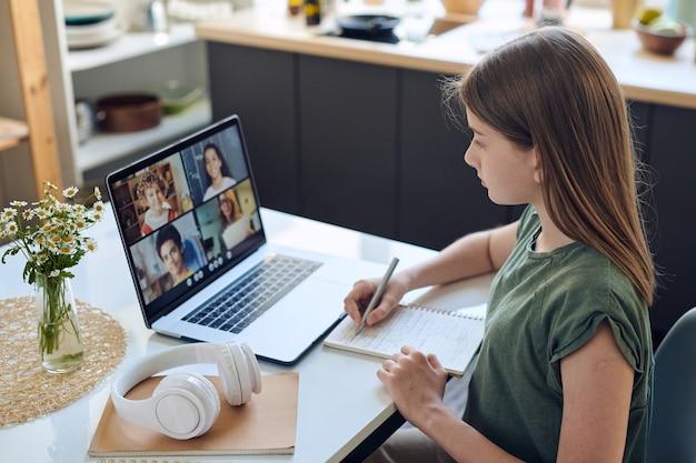 Blond slim schoolmeisje met pen over pagina van notitieblok kijkend naar haar leraar en klasgenoten op laptopscherm tijdens online les