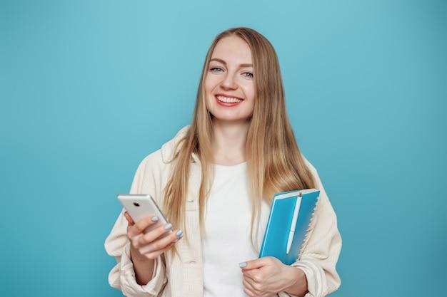Blond studentenmeisje die mobiele telefoon en blocnote houden en glimlachen geïsoleerd op blauwe muur. online onderwijs