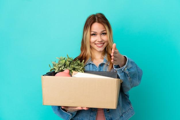 Blond tienermeisje dat een zet doet terwijl ze een doos vol dingen oppakt en handen schudt om een goede deal te sluiten