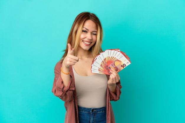 Blond tienermeisje dat veel euro's neemt over een geïsoleerde blauwe achtergrond die naar voren wijst en glimlacht