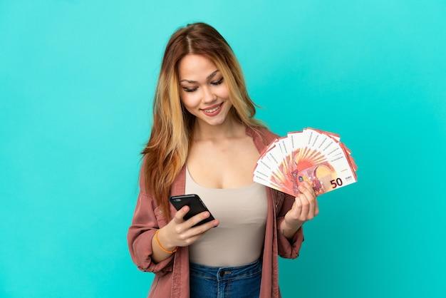 Blond tienermeisje dat veel euro's neemt over een geïsoleerde blauwe achtergrond met koffie om mee te nemen en een mobiel
