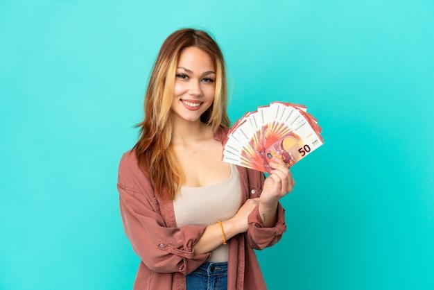 Blond tienermeisje dat veel euro's over een geïsoleerde blauwe achtergrond neemt en de armen gekruist houdt in frontale positie