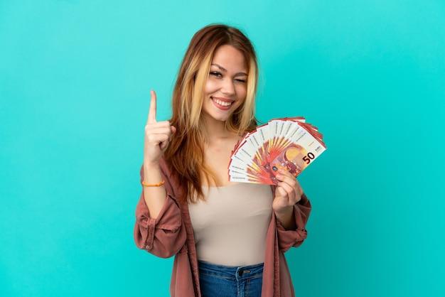 Blond tienermeisje dat veel euro's over een geïsoleerde blauwe achtergrond neemt en een geweldig idee benadrukt