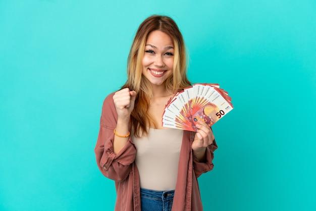 Blond tienermeisje dat veel euro's over een geïsoleerde blauwe achtergrond neemt en een overwinning in winnaarspositie viert