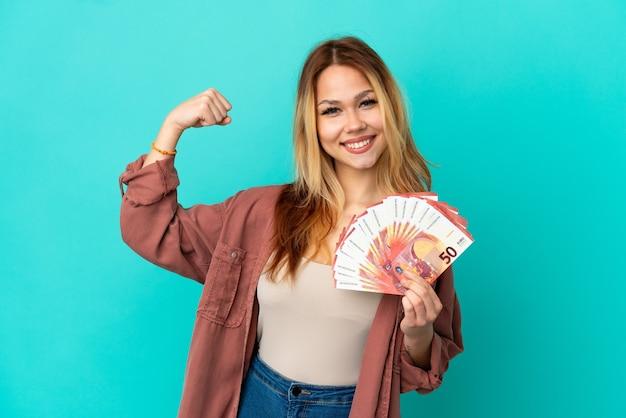 Blond tienermeisje dat veel euro's over een geïsoleerde blauwe achtergrond neemt en een sterk gebaar doet