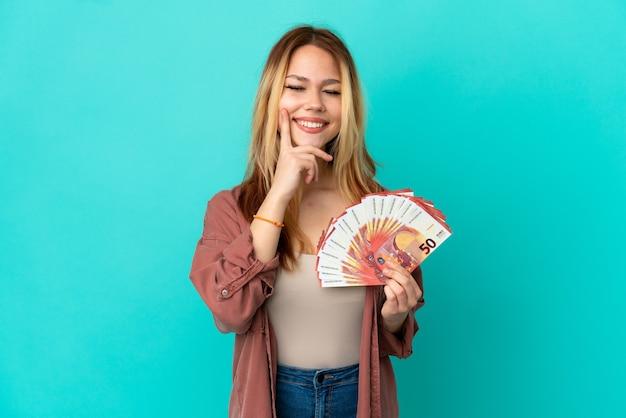 Blond tienermeisje dat veel euro's over een geïsoleerde blauwe achtergrond neemt en lacht met een gelukkige en aangename uitdrukking
