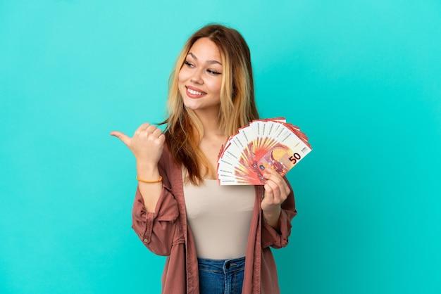 Blond tienermeisje dat veel euro's over een geïsoleerde blauwe achtergrond neemt en naar de zijkant wijst om een product te presenteren