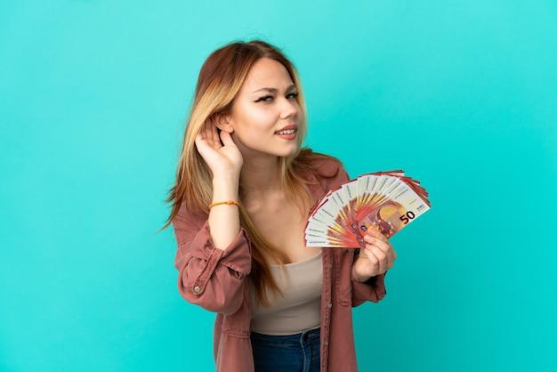 Blond tienermeisje dat veel euro's over een geïsoleerde blauwe achtergrond neemt en naar iets luistert door de hand op het oor te leggen