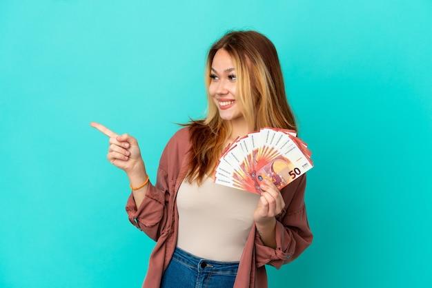 Blond tienermeisje dat veel euro's over een geïsoleerde blauwe achtergrond neemt, met de vinger naar de zijkant wijst en een product presenteert