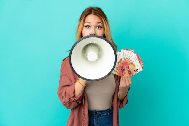 Blond tienermeisje dat veel euro's over een geïsoleerde blauwe achtergrond schreeuwt en door een megafoon schreeuwt