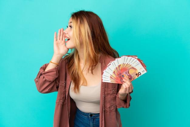 Blond tienermeisje dat veel euro's over een geïsoleerde blauwe achtergrond schreeuwt met wijd open mond naar de zijkant