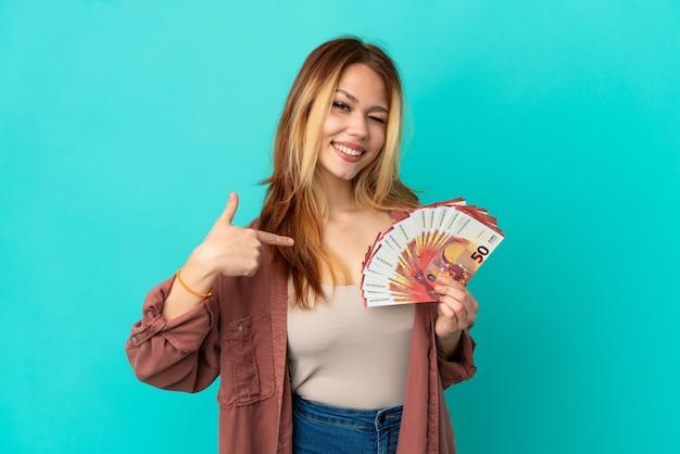 Blond tienermeisje dat veel euro's over geïsoleerde blauwe achtergrond neemt, trots en zelfvoldaan
