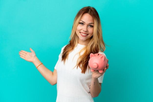Blond tienermeisje met een spaarpot over een geïsoleerde blauwe achtergrond die de handen naar de zijkant uitstrekt om uit te nodigen om te komen