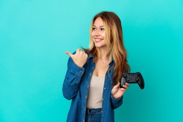 Blond tienermeisje speelt met een videogamecontroller over een geïsoleerde muur die naar de zijkant wijst om een product te presenteren