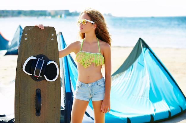 Blond vlieger tienermeisje in de zomer strand