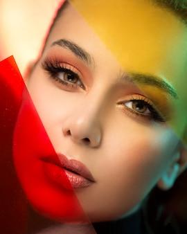 Blond vrouwelijk model dat make-up met rode en gele accenten draagt