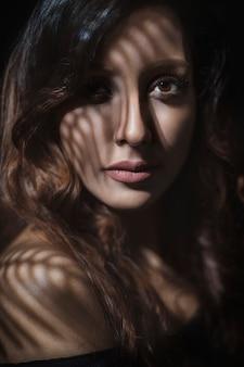 Blond vrouwelijk model in dagelijkse make-up in de schaduw
