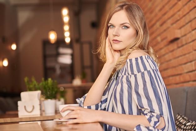 Blond vrouwenhaar met kopje koffie