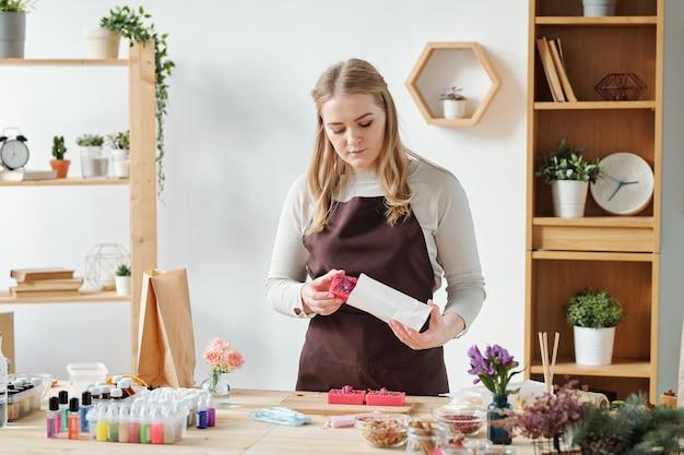 Blond wijfje die in schort met de hand gemaakte zeepstaaf in document pakket zetten om het aan iemand als gift voor vakantie te geven