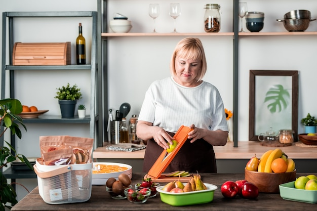 Blond wijfje in vrijetijdskleding die zich door keukentafel met verscheidenheid aan vers fruit bevindt en snijder gebruikt tijdens het bereiden van zelfgemaakte droge peren