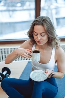 Blond zelfverzekerd jong meisje lacht en geniet van koffie in de ochtend in appartement zittend op tapijt met sportkleding op besneeuwde achtergrond.