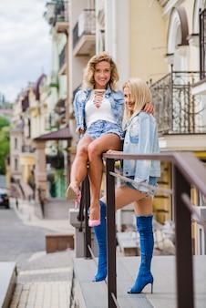Blonde aantrekkelijke meisjes poseren op straat