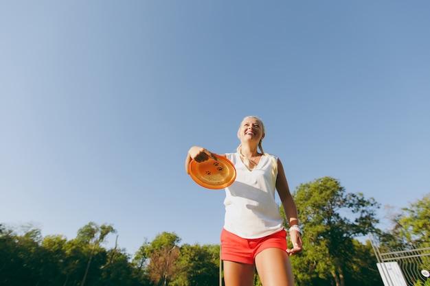Blonde aantrekkelijke sportieve vrouw gekleed in wit t-shirt en oranje korte broek gooien vliegende schijf naar kleine grappige hond, die het op het groene gras buiten in het park vangt