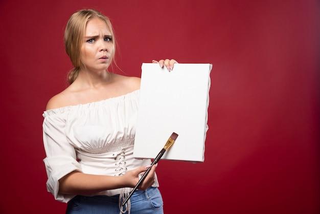 Blonde artiest toont haar kunstwerken en kijkt twijfelachtig.