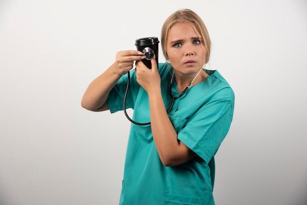 Blonde arts die een kopje koffie vasthoudt met een bange uitdrukking.