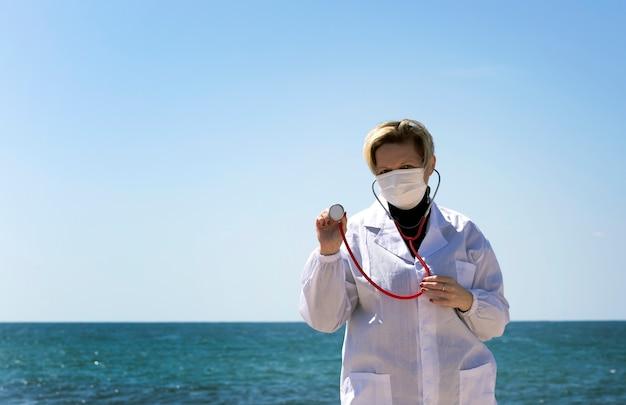 Blonde arts vrouw van russisch kaukasisch uiterlijk met een stethoscoop in de hand. portret van professionele zelfverzekerde amerikaanse arts met medisch masker en witte jas, stethoscoop over nek op een strand