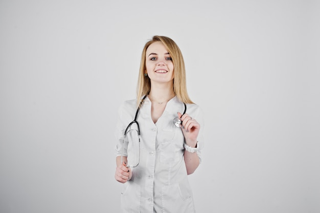 Blonde artsenverpleegster met stethoscoop op witte achtergrond wordt geïsoleerd die.